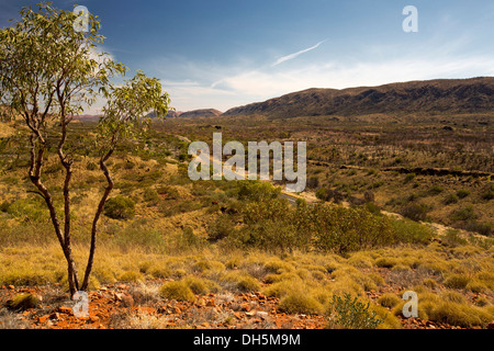 View of vast outback landscape, road, and West MacDonnell Ranges from lookout near Alice Springs in Northern Territory - Stock Photo