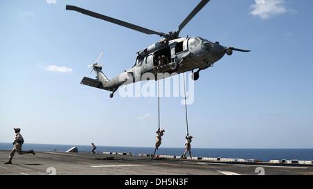 U.S. Marines with Battalion Landing Team 1/4 (BLT), 13th Marine Expeditionary Unit (MEU) conduct fast rope training - Stock Photo