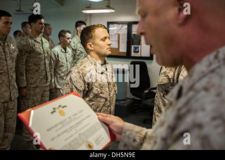 U.S. Marine Corps Sgt. Maj. Joel Collins, 22nd Marine Expeditionary Unit (MEU) sergeant major, reads the Navy and - Stock Photo