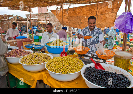 Young man selling olives in large bowls at his stall in the souks or bazaar area of Zagora, Draa Valley, Morocco, - Stock Photo