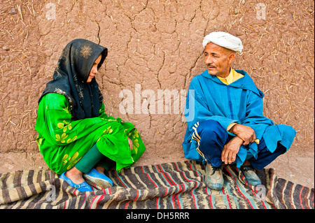Elderly man and a young girl, Berber people, squatting on a carpet or rug in front of a mud brick house talking - Stock Photo