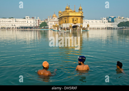 Golden Temple, Hari Mandir, the main shrine of the Sikh, three pilgrims wearing turbans taking a ritual bath in the holy lake of