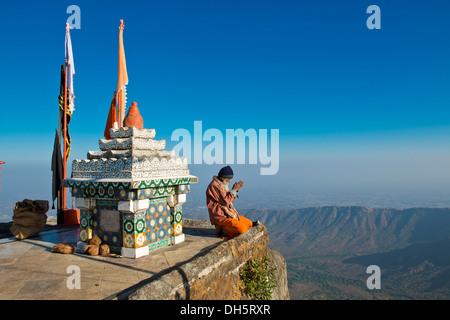 Sadhu or holy man sitting with his hands folded in prayer on the precipice in front of a Hindu temple shrine with - Stock Photo
