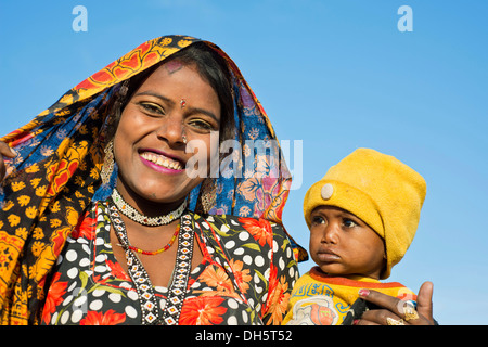 Smiling Indian women with a colourful scarf holding a small child in her arms, portrait, Pushkar, Rajasthan, India - Stock Photo