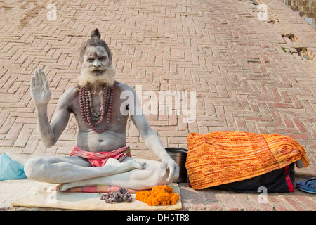 Sadhu, holy man or wandering ascetic sitting in the lotus position on a cloth, his body is smeared with white ashes - Stock Photo