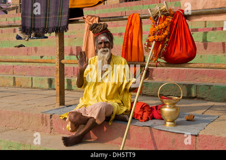 Elderly Sadhu, holy man or wandering ascetic sitting on a blanket on the steps on the bank of the Ganges River with - Stock Photo