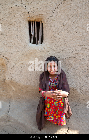 Smiling girl wearing a headscarf and traditional clothing sitting in front of a house wall with a window opening, - Stock Photo