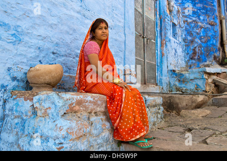 Elderly woman wearing a red sari sitting on a ledge of a blue painted residential building, Brahmpuri, Jodhpur, - Stock Photo
