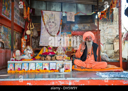 Sadhu, a holy man or wandering ascetic sitting in the lotus position on a mat in a Hindu prayer shrine, Pushkar, - Stock Photo