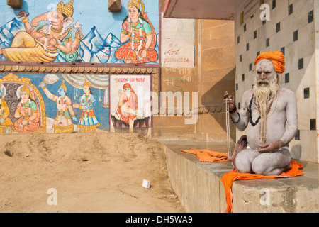 Sadhu, a holy man or wandering ascetic sitting meditating on a towel, his body is smeared with white ashes in the - Stock Photo