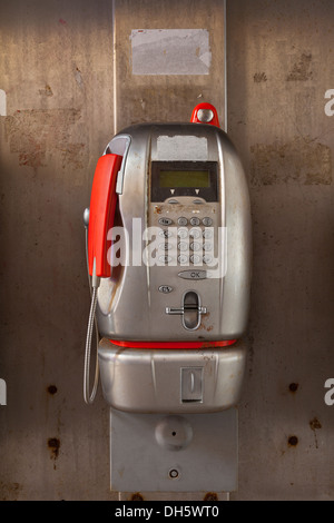 Aluminium public telephone with a red handset. - Stock Photo
