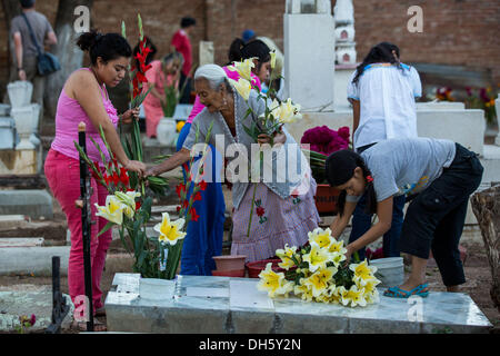 A Mexican family place flowers on the tomb of a family member during the Day of the Dead festival known in spanish - Stock Photo