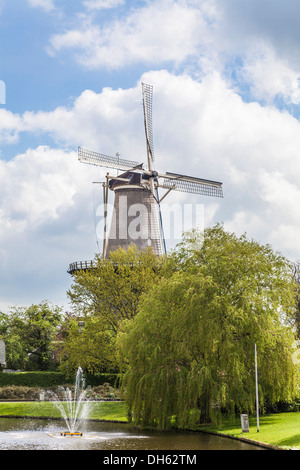 The traditional style Molen de Valk windmill, now a museum, in Leiden, Holland on the banks of a branch of the River - Stock Photo