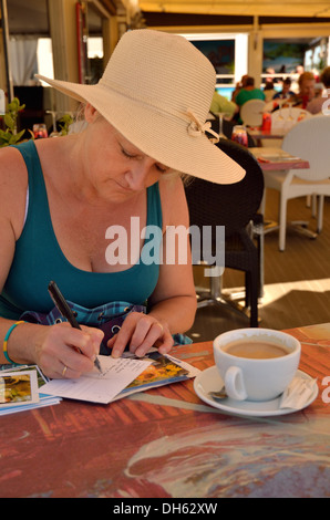 Mature woman on holiday writing postcards in a French cafe - Stock Photo