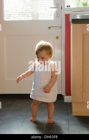 Nine month old girl learning to stand and walk on kitchen ...
