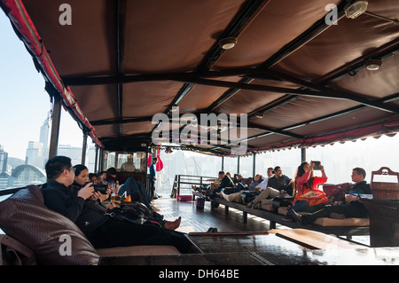 Tourists relaxing onboard a traditional junk ship in Hong Kong. - Stock Photo