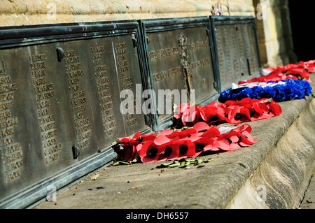 Wreaths of poppies laid next to names of fallen soldiers at the foot of the war memorial in Hinckley - Stock Photo