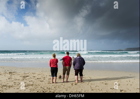 Three people standing on the beach at Sennen Cove. - Stock Photo