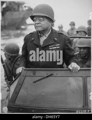 Brig. Gen. Benjamin O. Davis watches a Signal Corps crew erecting poles, somewhere in France. , 08-08-1944 531201 - Stock Photo