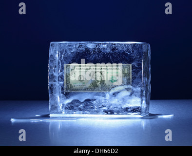 A one dollar US banknote frozen in a clear block of ice - Stock Photo