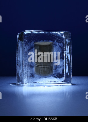 A black oil barrel frozen in a clear block of ice - Stock Photo