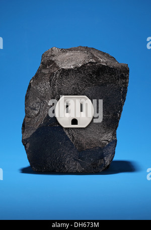 A large piece of black coal with a single electrical outlet. Bright blue background - Stock Photo
