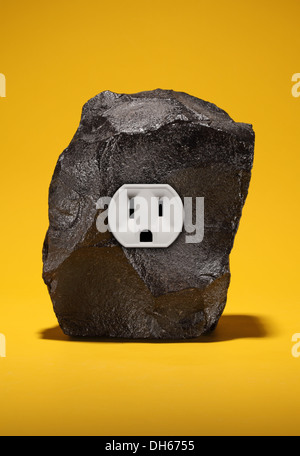 A large piece of black coal with a single electrical outlet. Bright yellow background. - Stock Photo
