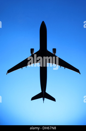 A plastic model of a commercial airplane airplane flying in blue sky - Stock Photo