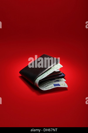 A black leather wallet filled with EU currency on a bright red background - Stock Photo