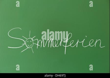 Sommerferien, German for summer vacation, written on a school blackboard - Stock Photo