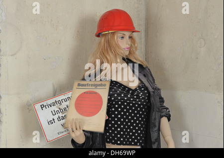 Mannequin with a hard hat on a building site, holding a construction approval and a 'no entry' sign in her hand. - Stock Photo