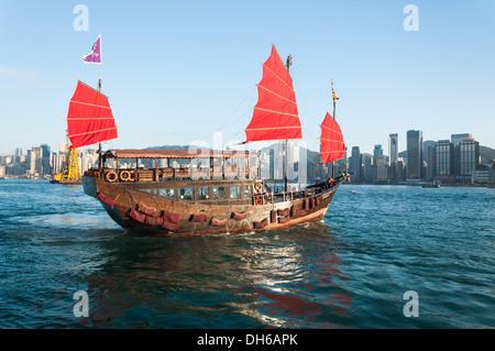 A traditional junk ship sails along Victoria Harbor in Hong Kong. - Stock Photo