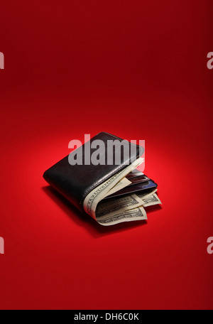 A black leather wallet filled with US currency on a bright red background - Stock Photo