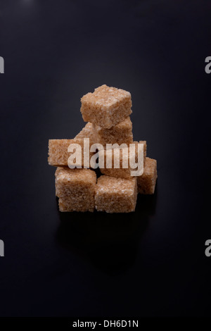 Photo of sugar cubes isolated on a black background - Stock Photo