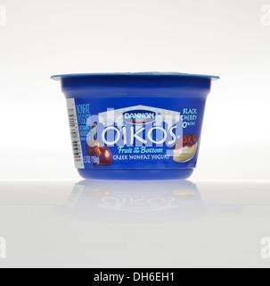 Unopened Dannon Oikos Greek black cherry Yogurt pot on white background, cutout. USA - Stock Photo