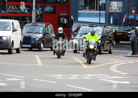Motorcyclists and other traffic entering the roundabout by Waterloo Bridge, in London, England. - Stock Photo