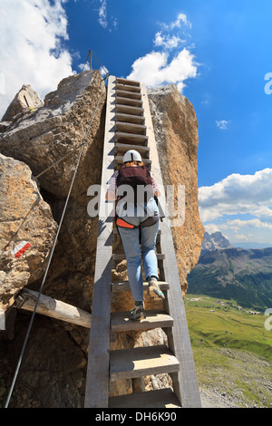 hiker on a big wooden ladder in Bepi Zac via ferrata, Trentino, Italy - Stock Photo