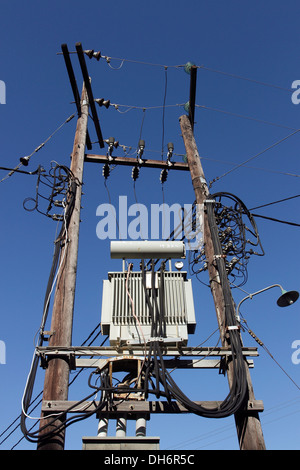Complex electrical wiring and a sub-station supported on two poles on the Greek Island of Skiathos in the Aegean - Stock Photo
