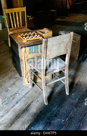 Checker board game set up, ready to play, on an old crate in a warehouse barn between two beat up old wood chairs. - Stock Photo