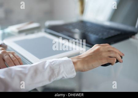Woman's hand using cordless mouse on glass table - Stock Photo