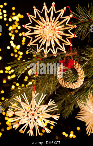 Fragile handmande straw christmas ornaments hanging in the tree - Stock Photo