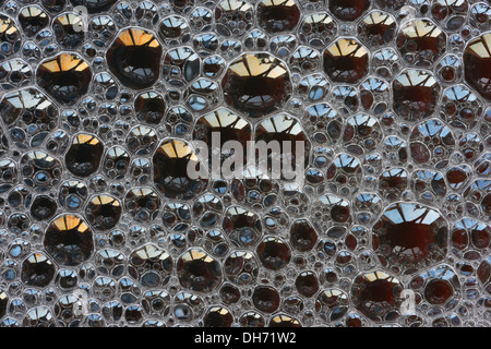 Bubbles with spectral colors being diffracted through thin surface film and refraction of light in water floating - Stock Photo
