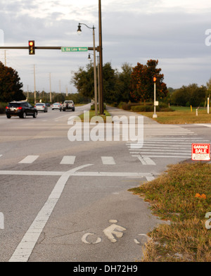 Cycle track markings on at a busy interstate high intersection, Partly worn out partly overgrown, November 2013 - Stock Photo