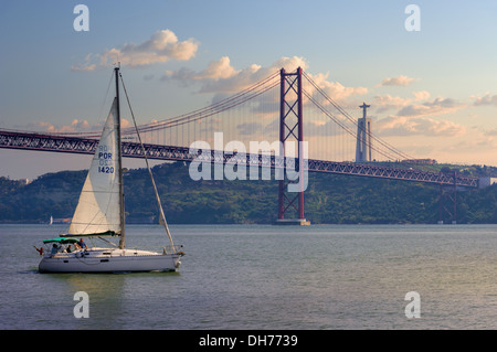 Portugal, Lisbon, the Cristo Rei monument and the Ponte 25 de Abril bridge at dusk - Stock Photo
