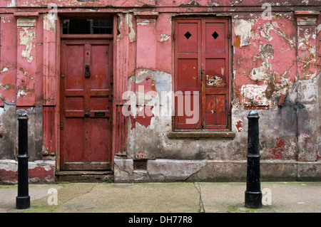 The peeling and dilapidated looking exterior of a house in Princelet Street, Spitalfields. - Stock Photo