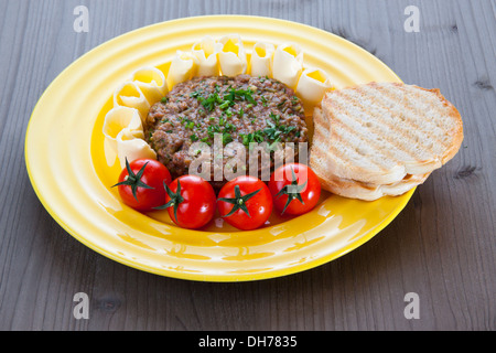 Steak tartare with toasted bread, tomatoes and butter on yellow plate - Stock Photo