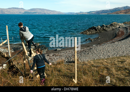Two walkers crossing a stile on a deer fence on the coastal path to Inverguseran.  Knoydart, Highland region, Scotland, - Stock Photo