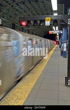 A subway train in motion as it arrives at Stillwell Avenue Station at night in Coney Island, Brooklyn - Stock Photo