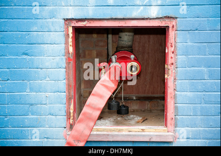 Fire hose feeding dry riser inlet valve - Stock Photo