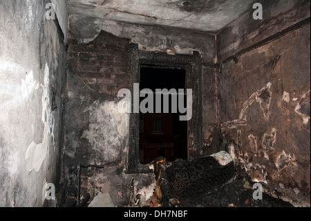 Burnt out house bedroom severe hot fire brick exposed - Stock Photo